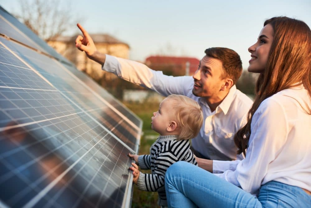 family inspecting a solar panel